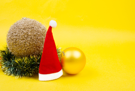 Small Santa hat, golden Christmas balls and a Christmas wreath on the bright yellow background as the Christmas concept (copy space on the right for your text)