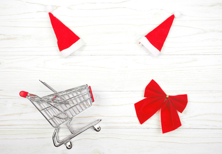 Shopping cart, two Santa hats and a red Christmas bow forming a frame on a white wooden background as the Christmas sale concept (top view, copy space in the center for your text)