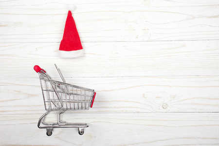 Shopping cart and a Santa hat on a white wooden background as the Christmas sale concept (top view, copy space on the right for your text) Stockfoto - 112880941