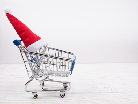 Shopping cart with a Santa hat on a white wooden background as the Christmas sale concept (copy space on the right for your text)
