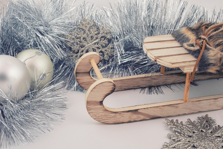 Christmas or New Year decorations (silver tinsel, snowflakes and a wooden toy Christmas sleigh on a white wooden background), retro toned, vintage style Stockfoto - 112880954