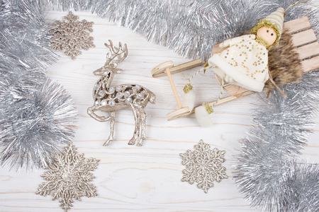 Toy Christmas elf on a wooden Christmas sleigh, toy reindeer, silver tinsel and snowflakes on a white wooden background (isolated on white), top view Stockfoto - 112880955