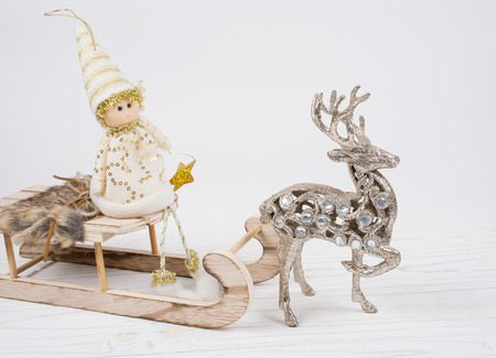 Toy Christmas elf sitting on a wooden Christmas sleigh and a reindeer on a white wooden background (isolated on white), copy space on the right for your text Stockfoto - 112880957