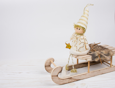 Toy Christmas elf sitting on a wooden Christmas sleigh on a white wooden background (isolated on white), copy space on the left for your text Stockfoto - 112880958