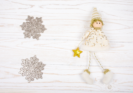 Two silver snowflakes and a cute toy Christmas elf on a white wooden background (isolated on white), top view, copy space in the center for your text