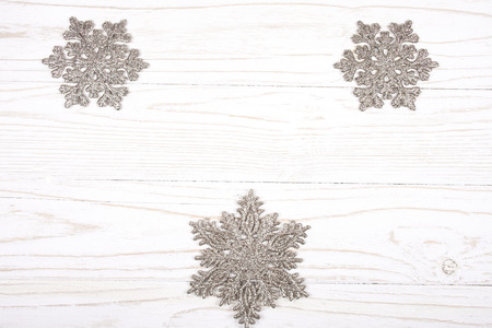 Snowflakes as Christmas decorations on a white wooden background (top view, copy space in the center for your text) Stok Fotoğraf