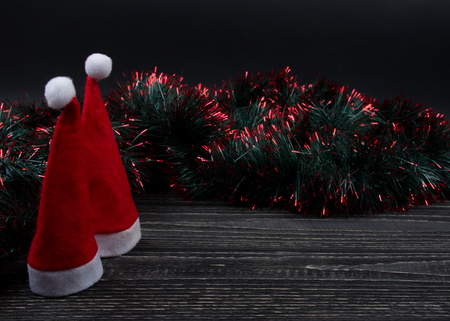 Two Santa hats and green and red tinsel on a black wooden background as a New Year or Christmas composition (copy space for your text, selective focus on Santa hats)