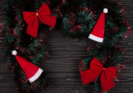 Santa hats, red Christmas bows and green and red tinsel forming a frame on a black wooden background as a New Year or Christmas background (top view, copy space in the center for your text) Stockfoto - 112880962