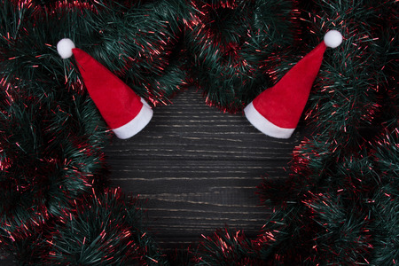 Two Santa hats and green and red tinsel forming a frame on a black wooden background as a New Year or Christmas background (top view, copy space in the center for your text)