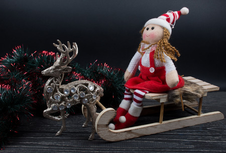 Doll wearing a Christmas outfit and sitting on a wooden Christmas sleigh, a toy reindeer and green and red tinsel on a black wooden background (isolated on black)