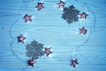 Garland with Christmas lights in the shape of stars forming a frame on a wooden background, copy space in the center (in blue tones)