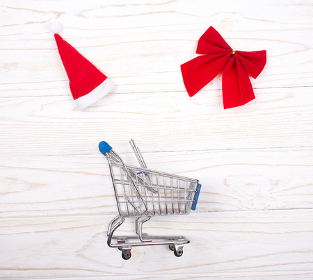 Shopping cart, a Santa hat and a red Christmas bow forming a frame on a white wooden background as the Christmas sale concept (top view)