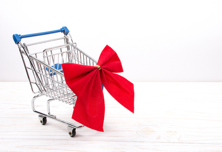 Shopping cart with a red bow on a white wooden background as the Christmas sale concept (copy space on the right for your text) Stock Photo