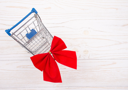 Shopping cart with a red bow on a white wooden background as the Christmas sale concept (top view, copy space on the right for your text)