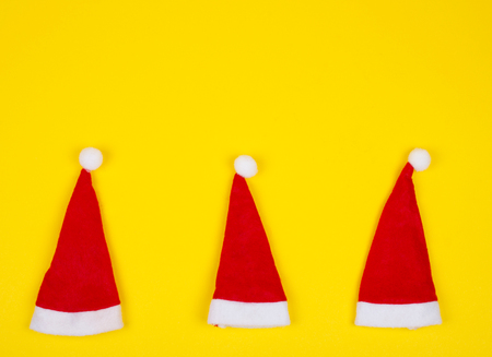 Three small Santa hats on the bright yellow background as the Christmas concept (top view, minimal style), copy space for your text