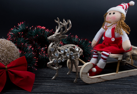 Doll wearing a Christmas outfit and sitting on a wooden Christmas sleigh, toy reindeer, green and red tinsel, Christmas ball and red Christmas bow on a black wooden background (isolated on black)