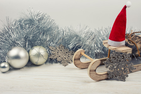 Christmas or New Year decorations (wooden toy Christmas sleigh with a Santa hat, silver tinsel, snowflakes and Christmas balls on a white wooden background), copy space for your text, retro style