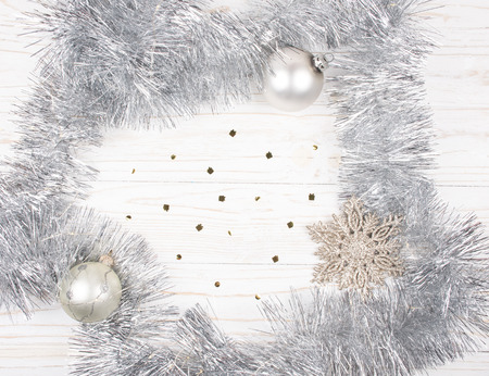 Christmas or New Year decorations (silver tinsel, garland with Christmas lights, snowflake and Christmas balls) on a wooden background, copy space in the center