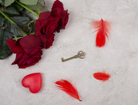 Bouquet of bright red roses, a heart, a key and red feathers on a gray marble background (top view) as the love and sensuality concept