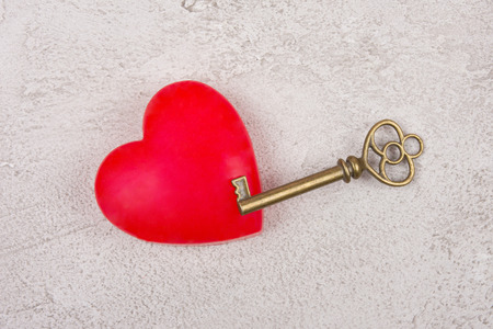 Bright red heart and an old antique key on a gray marble or concrete background (top view) as the Valentine day or love concept