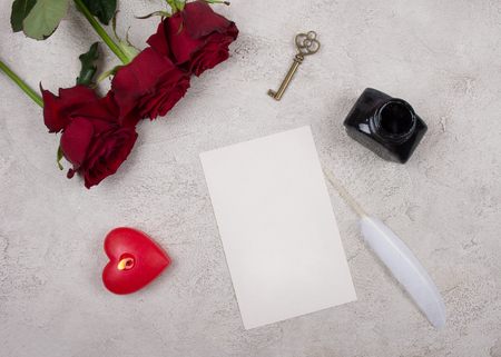 Red roses, a heart-shaped candle, a key, a blank card, a white feather and an inkpot on a gray marble or concrete background (top view) as the Valentine day or love concept