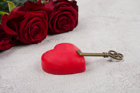 Heart and a key against the background of red roses (as the Valentine day or love concept)