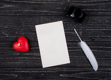 Heart-shaped candle, a blank card, a white feather and an inkpot on a black wooden background (top view) as the Valentine day or love concept Stok Fotoğraf