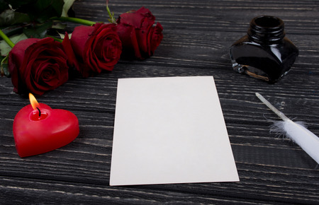 Red roses, a heart-shaped candle, a blank card, a white feather and an inkpot on a black wooden background as the Valentine day or love concept Stok Fotoğraf