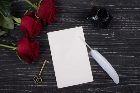 Red roses, a key, a blank card, a white feather and an inkpot on a black wooden background (top view) as the Valentine day or love concept Stockfoto - 112881039