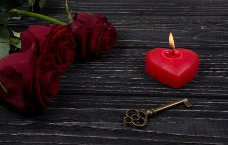 Red roses, a heart-shaped candle and a key on a black wooden background as the Valentine day or love concept