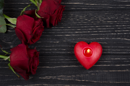Red roses and a red heart-shaped candle on a black wooden background as the Valentine day or love concept Stockfoto - 112881041