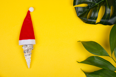 Seashell wearing a Santa hat and tropical leaves on the bright yellow background as the tropical Christmas concept (copy space in the center for your text)