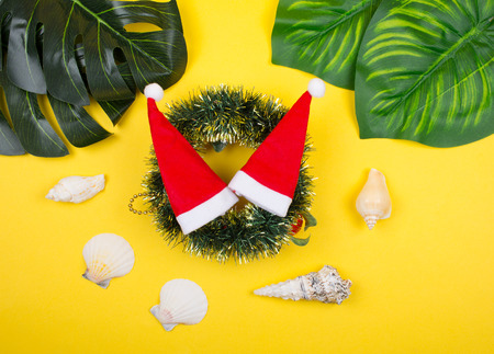 Two small Santa hats on a Christmas wreath among tropical leaves and seashells on the bright yellow background as the tropical Christmas concept