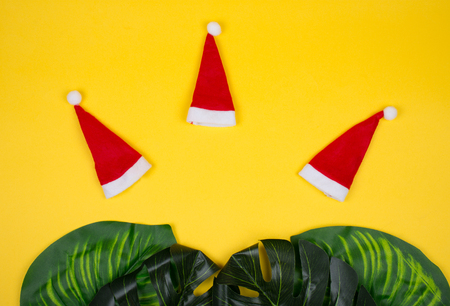 Three small Santa hats and tropical leaves on the bright yellow background as the tropical Christmas concept (copy space in the center for your text) Stock Photo