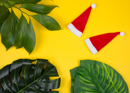 Two small Santa hats and tropical leaves on the bright yellow background as the tropical Christmas concept (copy space in the center for your text) Stok Fotoğraf