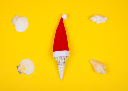 Seashell wearing a Santa hat and scattered shells on the bright yellow background as the tropical Christmas concept (top view, minimal style) Stockfoto - 112881088