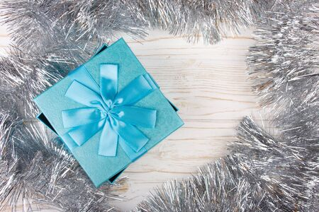 Blue gift box and silver tinsel on the white wooden background (flat lay, copy space for your text) Stockfoto