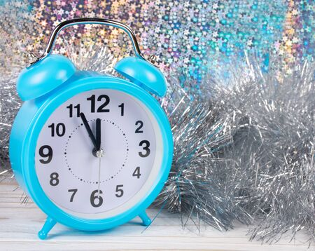 Blue clock showing almost midnight as a New Year concept (against the shiny multicolored background and silver tinsel) Standard-Bild - 135205604
