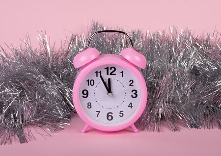 Pink clock showing almost midnight as a New Year concept (in silver tinsel against the pink background) Stockfoto