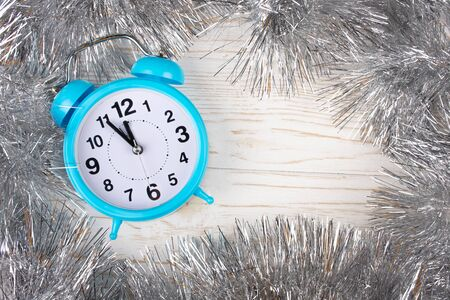 Blue clock showing almost midnight as a New Year concept (in silver tinsel on the white wooden background, flat lay, copy space in the center for your text)