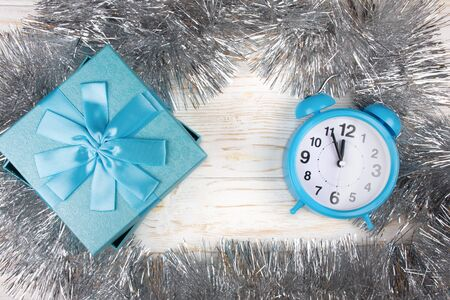 Blue gift box and a blue clock showing almost midnight (in silver tinsel on the white wooden background, flat lay, copy space in the center for your text) Standard-Bild - 135515099