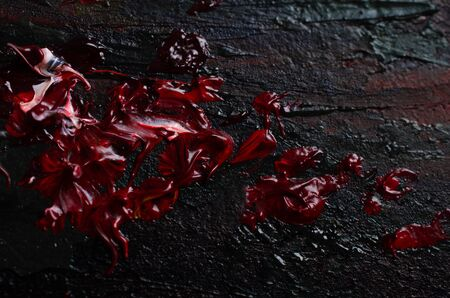 Smears of red paint resembling blood on a black background