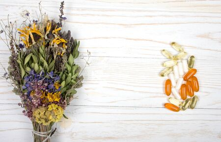 Bouquet of herbs and a pile of pills on a white wooden background (as the concept of herbal medicine versus modern medicine or herbs versus drugs), top view, copy space in the center for your text
