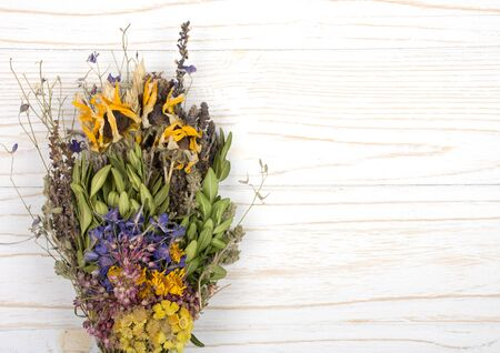 Bouquet of dry herbs on a white wooden background (as the herbal medicine concept), top view, copy space on the right for your text