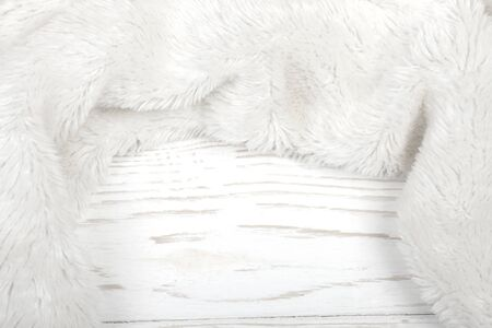 White fur on a white wooden background as a white winter or New Year background (with copy space in the center), selective focus Stockfoto