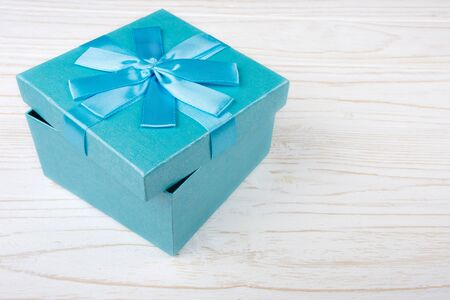 Blue gift box on the white wooden background (copy space for your text)
