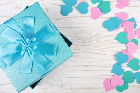 Blue gift box and a pile of paper hearts of pastel colors on the white wooden background (flat lay, copy space in the center for your text)