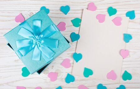 Blue gift box, paper hearts of pastel colors and a blank greeting card on the white wooden background (flat lay)
