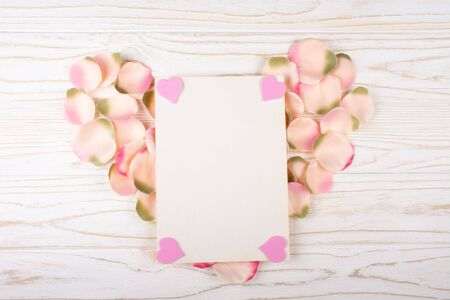 Blank greeting card with pink hearts in corners on a heart-shaped pile of handmade rose petals (on the white wooden background, flat lay)