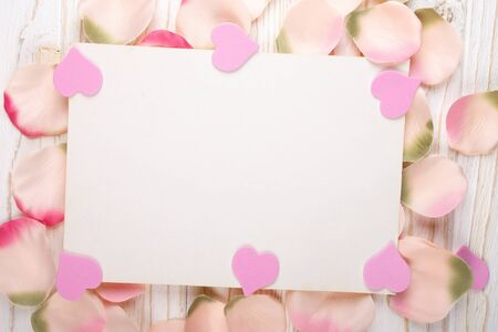 Blank greeting card with pink hearts on a pile of handmade rose petals (on the white wooden background, flat lay)